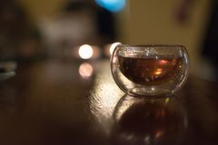 Transparent small glass of Chinese black tea on a table, shot co royalty free stock image