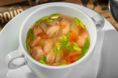 Transparent soup with chicken, carrots and greens stock photo