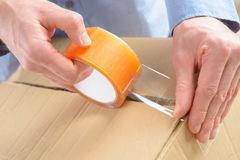 Transparent tape. Hands with roll of transparent packaging, adhesive tape on a cardbox Stock Image