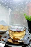 Transparent tea cup against window with rainy day view. Dried fruit tea cup against window with rain drops royalty free stock images