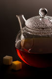 Transparent teapot with black tea and sugar Royalty Free Stock Image