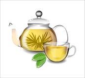 Transparent teapot and a cup of  tea. Stock Photos