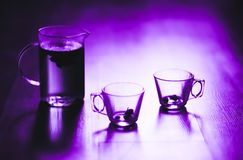 Transparent teapot and cups on a lilac background with copy space royalty free stock images