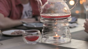 Transparent teapot heated candle in a cafe, people at the table. HD stock video