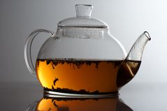 Transparent teapot with herb tea Stock Image