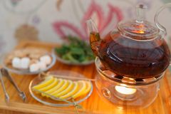 Transparent teapot kettle with tasty black tea on stand with candles. On plates the lemon, sugar, mint and thyme. On colored backg. Round. Shallow depth of field Royalty Free Stock Photos