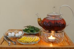 Transparent teapot kettle with tasty black tea on stand with candles. On plates the lemon, sugar, mint and thyme. On wooden backgr. Ound. Horizontally framed Royalty Free Stock Photos