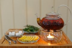 Transparent teapot kettle with tasty black tea on stand with candles. On plates the lemon, sugar, mint and thyme. On wooden backgr. Ound. Shallow depth of field Stock Photo