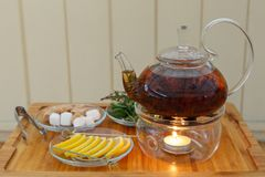 Transparent teapot kettle with tasty black tea on stand with candles. On plates the lemon, sugar, mint and thyme. On wooden backgr. Ound. Horizontally framed Royalty Free Stock Photography