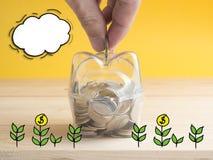 Transparent voir la tirelire remplie de pièces de monnaie sur le fond en bois Concept coloré d'investissement d'économie Main met Photo stock