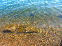 Transparent water of Lake Baikal. Transparent blue water and stones of Lake Baikal Royalty Free Stock Photography