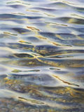 Transparent water watercolor. Sea view background. Blue sea or ocean transparent shallow water over pebble bottom of stony beach coast. Wave is incident on the Royalty Free Stock Images