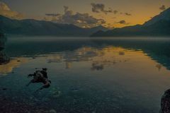 Transparent waters of a lake surrounded by mountains. You can see a sunrise reflected on the transparent waters of a lake and in the background the mountains stock photo