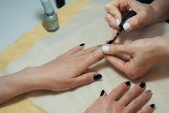 Transparente Beschichtung der Nägel ist eine Nahaufnahme im Schönheitssalon Maniküreprozeß? Die Frauhände? stockbild
