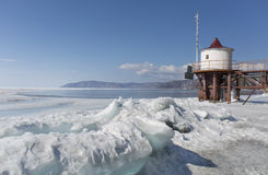Transparente blaue Eishügel auf der Baikalsee-Ufer Sibirien-Winterlandschaftsansicht mit Leuchtturm Schneebedecktes Eis von Lizenzfreie Stockfotos