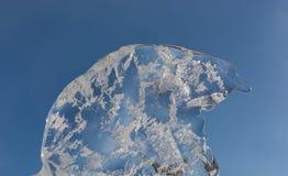 Transparente blaue Eisscholle gegen den blauen Himmel Frühlingszeit… Rosenblätter, natürlicher Hintergrund stockbilder