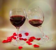 Transparente Gläser mit Rotwein und Textilroten Valentinsgrußherzen, heller Blendenfleckhintergrund, Abschluss oben Stockbild