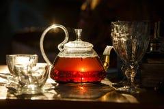 Transparente Glasteekanne mit schwarzem Tee glüht in die Sonne die las Lizenzfreie Stockbilder