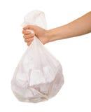Transparente Plastiktasche mit Papierabfall in der weiblichen Hand lokalisiert Lizenzfreie Stockfotos