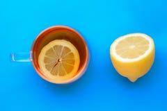 Transparente Tasse Tee mit Zitrone, schnitt frisch halbe Zitrone auf blauem Hintergrund stockbild