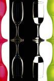 Transparente y las copas de vino rojo-verdes en el fondo blanco y negro con la reflexión. Foto de archivo