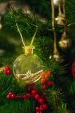 Transparenter Ball mit einem Schlüssel und ein Buchstabe im goldenen Sand, hängend an einem Weihnachtsbaum Stockbilder