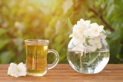 Transparenter Becher Tee und ein Vase mit Jasmin auf einem Holztisch, Grüns auf dem Hintergrund Lizenzfreies Stockbild