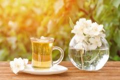 Transparenter Becher Tee und ein Vase mit Jasmin auf einem Holztisch, Grüns auf dem Hintergrund Stockfotos