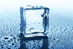 Transparenter Eiswürfel mit Reflexion auf blauem Glas mit Wasser fällt Lizenzfreies Stockbild