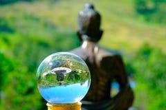 Transparenter Glasball auf hinterer Ansicht von Buddha-Statue mit Berg Stockbild