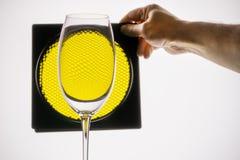 transparentes Glas hält Hand auf einem Hintergrund der gelben Bienenwabe stockfotografie