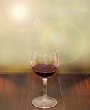 Transparentes Glas mit Rotwein, heller Blendenfleckhintergrund, hölzerne Beschaffenheitstabelle, Abschluss oben Lizenzfreies Stockbild