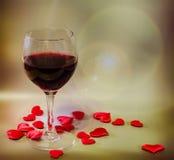 Transparentes Glas mit Rotwein und Textilroten Valentinsgrußherzen, heller Blendenfleckhintergrund, Abschluss oben Stockfoto