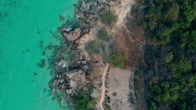 Transparentes Ozeanwasser durch braune felsige Küstenlinie und Wald stock footage