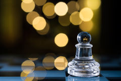 Transparentes Pfand auf blauem Schachbrett mit Bokeh Stockfotografie