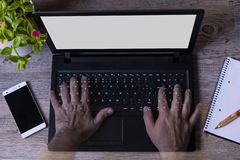 Transparents de las manos de un hombre en tabla de madera de la planta del cuaderno del teléfono del ordenador foto de archivo libre de regalías