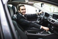 Transport, affärstur, destination och folkbegrepp - som är nära upp av ung man i dräkten som kör bilblick på kameran royaltyfria bilder