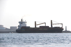Transport boat. Commercial cargo ship leaving the bay Stock Image