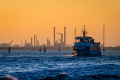Transport boat leaving the petroleum refinery during sunset Royalty Free Stock Image