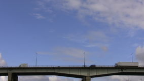Transport on the bridge. Distant side view of the transport on the bridge against the sky stock video footage