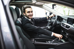 Transport, business trip, destination and people concept - close up of young man in suit driving car look at camera. Transport, business trip, destination and Royalty Free Stock Images