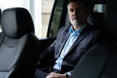 Transport, business trip and people concept - senior businessman driving on car back seat. royalty free stock images