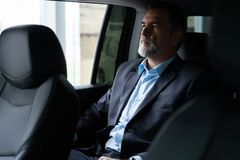 Transport, business trip and people concept - senior businessman driving on car back seat. stock images