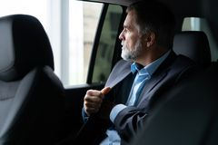 Transport, business trip and people concept - senior businessman driving on car back seat. royalty free stock image