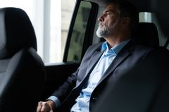 Transport, business trip and people concept - senior businessman driving on car back seat. stock image
