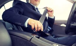 Senior businessman fastening car seat belt stock images