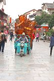 Transport of stacked chairs in West Street,Yangshuo, China. Man drives a scooter with carrier cycle which is loaded with a huge pile of stacked  chairs for Stock Images