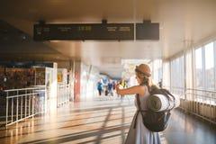 Transport en commun de voyage de thème position de jeune femme avec le dos dans la robe et le chapeau derrière le sac à dos et l' photos stock