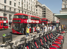 Transport Galore. People at a bus stop in Piccadilly, London next to a Cycle Hire stand and tube station royalty free stock photography