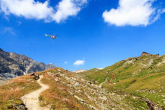 Transport helicopter flying with supplies and mountain panorama with alpine hut, Hohe Tauern Alps, Austria. Transport helicopter flying with supplies and Royalty Free Stock Photo